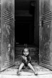 Dziewczynka-siedzaca-w-drzwiach-domu-w-Deli
